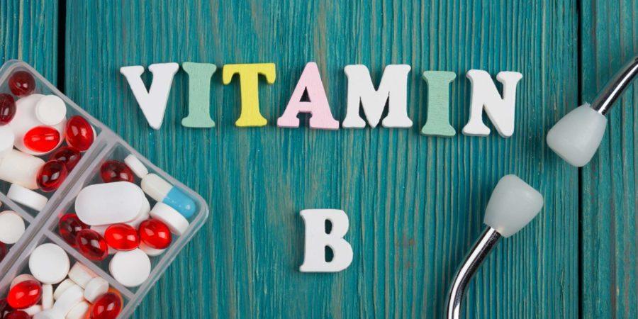 """Text """"Vitamin B"""" aus farbigen Holzbuchstaben, Stethoskop und Pillen auf blauem Holzhintergrund"""