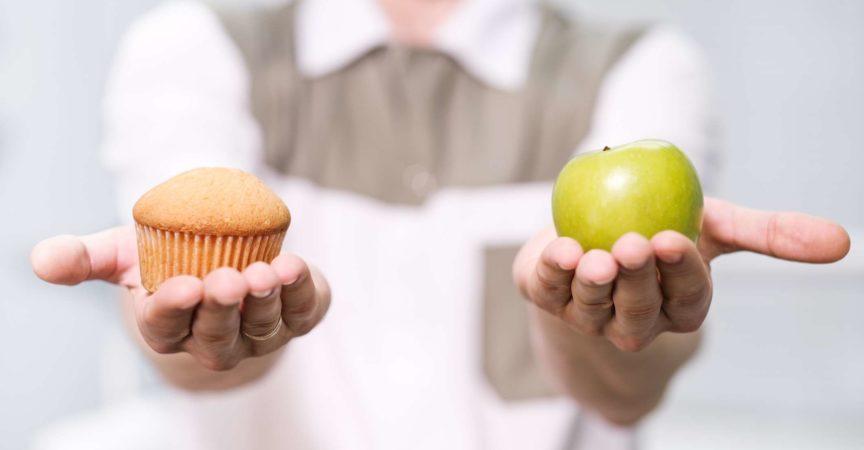 Doktor ein Zahnarzt ein Mann hält einen grünen Apfel und einen süßen Cupcake und zeigt auf der Waage eine Auswahl von nützlich gegen schädlich