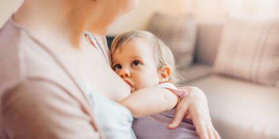 Mutter, die Kleinkindtochter stillt
