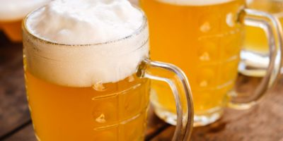 Nahaufnahme zwei kalte Biere mit Schaum und Wassertropfen auf altem Holztisch im Freien mit Sonnenstrahl