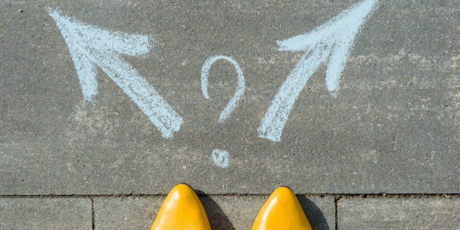 Weibliche Beine mit 2 Pfeilen und Fragezeichen, auf den Asphalt gemalt.