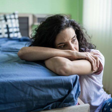 Mittlere erwachsene Frau, die allein zu Hause sitzt, besorgt.