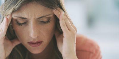Aufnahme einer attraktiven jungen Frau, die zu Hause unter starken Kopfschmerzen leidet