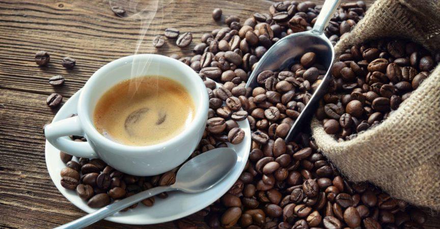 Tasse Espresso mit Kaffeebohnen, Beutel, Schaufel und Dampf auf rustikalem hölzernem Hintergrund