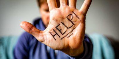 Mann hält Hand zur Kamera mit HILFE auf Handfläche geschrieben.