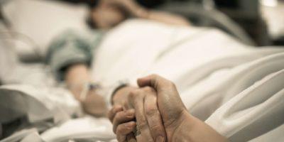 Kranke Frau, die im Krankenhausbett mit der Hand liegt, die von der Liebe gehalten wird. Familienlinien und medizinisches Tragödiekonzept.