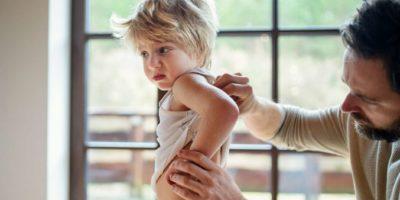 Vater mit einem kleinen kranken unglücklichen Sohn drinnen zu Hause, der seinen verletzten Rücken überprüft.