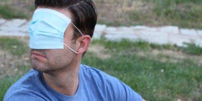 Mann, der seine Vision mit chirurgischer Maske bedeckt.