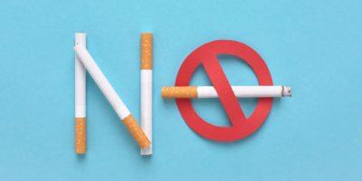 Nichtraucher-Symbol. Rotes verbotenes Zeichen mit einer Zigarette und dem Text, der auf blauem Hintergrund nicht raucht.