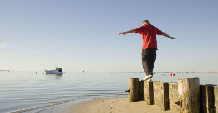 Mann, der einen Spaziergang auf dem Strand an einem Sommerabend nimmt.