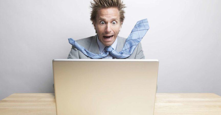 Überraschter Geschäftsmann Büroangestellter sitzt an seinem Schreibtisch und schaut auf seinen Computerbildschirm