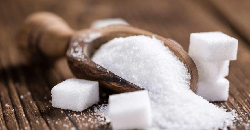 Teil des weißen Zuckers (detaillierte Nahaufnahme; selektiver Fokus) auf hölzernem Hintergrund