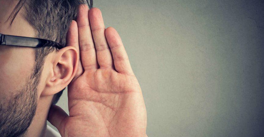 Mann hält seine Hand nahe Ohr und hört sorgfältig isoliert auf grauem Wandhintergrund zu
