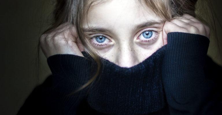 Besorgtes und verängstigtes Mädchen, das ihr Gesicht versteckt