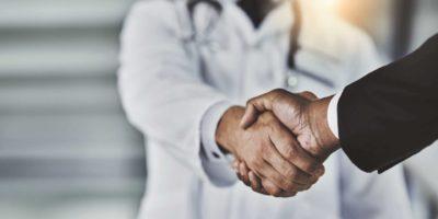 Kurzer Schuss eines Arztes, der einem Geschäftsmann in einem Krankenhaus die Hand schüttelt