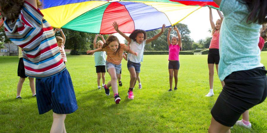 Kinder spielen mit einem bunten Fallschirm