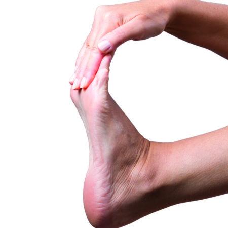 Schmerzen im fuß. Massage weiblicher Füße auf grauem Hintergrund