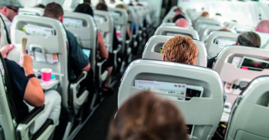 Innenraum eines Verkehrsflugzeugs mit Passagieren in ihren Sitzen während des Fluges.