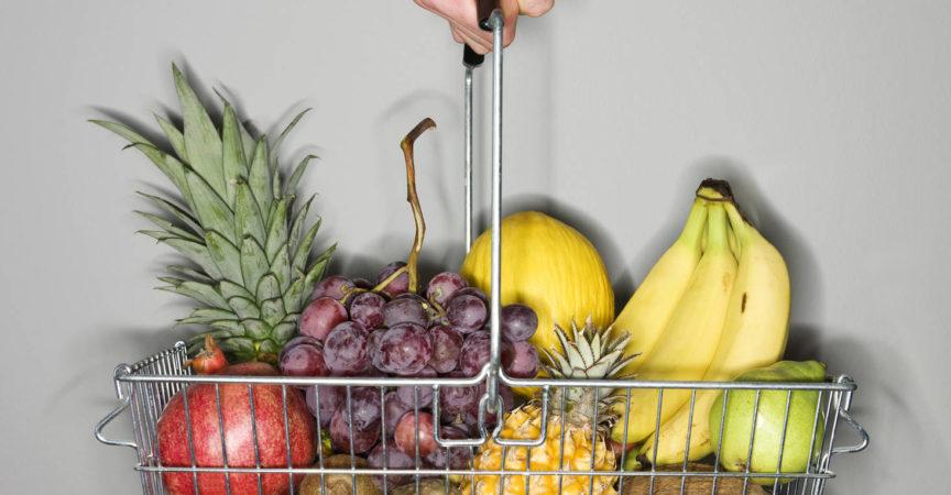 Einkaufskorb mit Früchten auf grauem Hintergrund