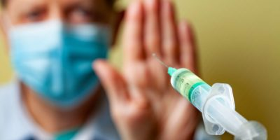 Eine Hand haltend, um die Annäherung einer COVID-19-Impfspritze zu verhindern, steht eine Anti-Vaxxer-Person im Hintergrund