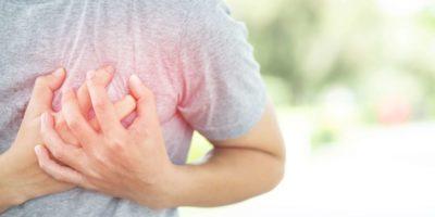 Beide Hände umfassen die linke Brust einer Person mit Brustschmerzen.