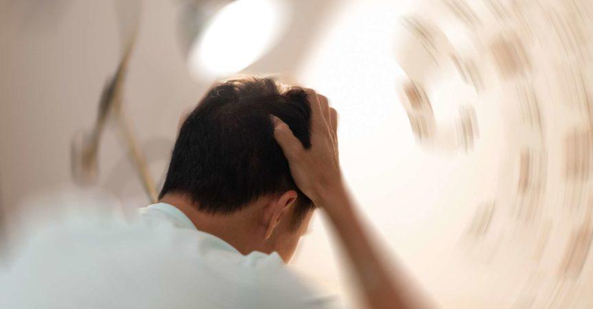 Konzept der Schwindelkrankheit. Mann Hände auf den Kopf fallen Kopfschmerzen Schwindelgefühl Drehschwindel, ein Problem mit dem Innenohr, dem Gehirn oder der sensorischen Nervenbahn.
