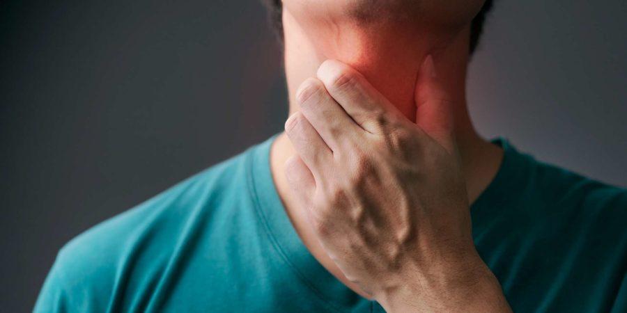 Unglücklicher asiatischer Mann, der seine Hand an seinem Hals berührt und an Drüsenentzündung leidet. Erwachsener Mann fühlt sich schlecht an Halsschmerzen und krank von Erkältung, Grippe. Halsschmerzen, Krankheit, Gesundheitswesen und medizinisches Konzept.