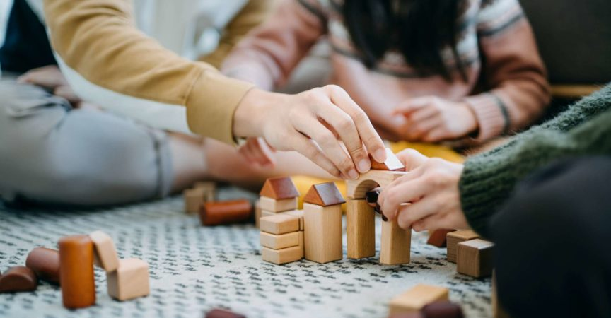Nahaufnahme von fröhlichen asiatischen Eltern, die im Wohnzimmer auf dem Boden sitzen und Spaß haben und mit ihrer Tochter zusammen Holzbausteine spielen?
