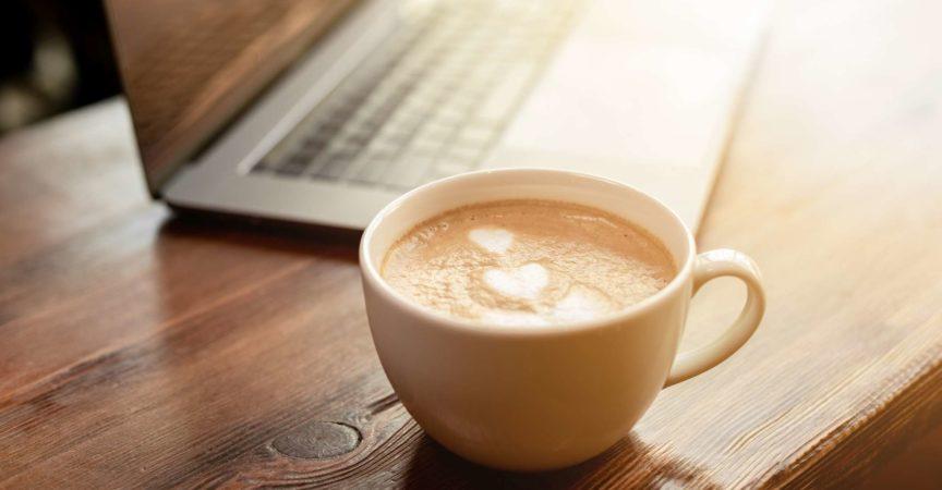 Tasse Kaffee-Cappuccino mit grauem Laptop auf Holztisch. Geschäftskonzept