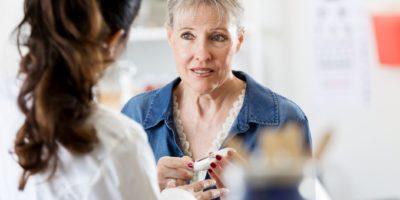 Eine besorgte ältere Frau hält ein Glaukometer, während sie mit einer Ärztin über ihre Diabetes-Diagnose spricht.