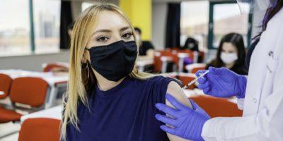 Krankenschwester gibt Schülern während der Coronavirus-Pandemie eine Impfung in der Schule