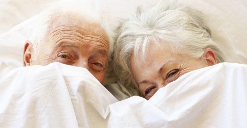 Älteres Paar, das sich im Bett versteckt, das unter Laken lächelt und lacht.