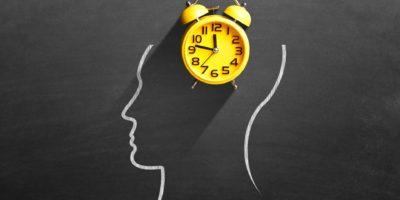 Gelber Wecker vor dem menschlichen Gehirn auf der Tafel, der das Konzept des Zeitmanagements darstellt.