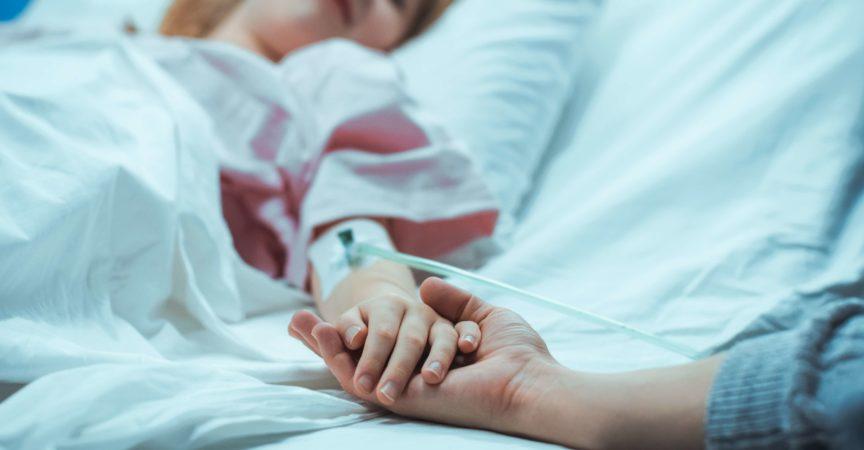 Das kleine Kind, das im Krankenhausbett schläft, erholt sich, ihre Hand fällt in die Mutter und sie hält sie tröstend. Konzentrieren Sie sich auf die Hände. Emotionaler Familienmoment.