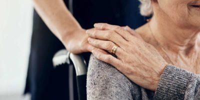 Abgeschnittene Aufnahme einer weiblichen Pflegekraft, die eine ältere Frau tröstet