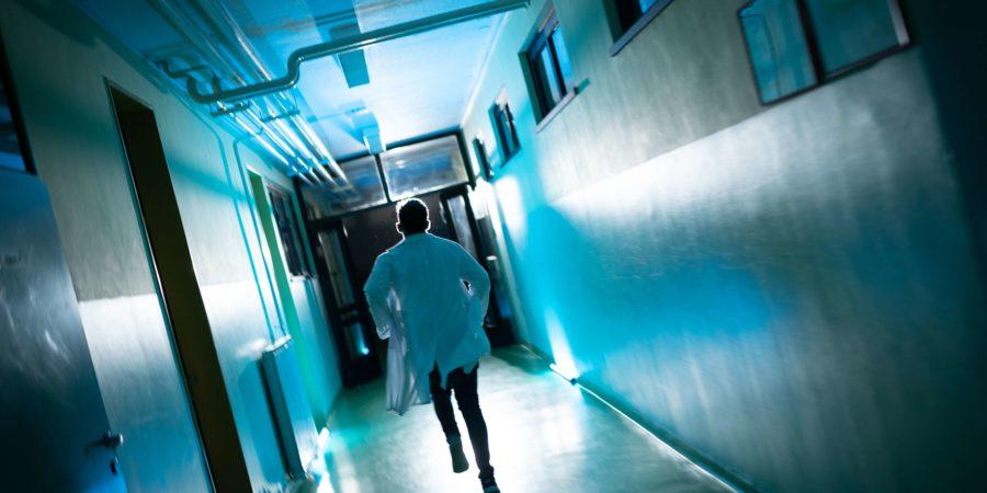 Rückansicht des männlichen Arztes, der den Flur der Krankenstation hinuntereilt, um zum Patienten zu gelangen