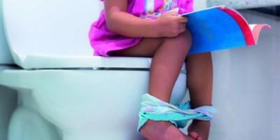 Kleines Kind sitzt auf der Toilette und liest ein Buch.