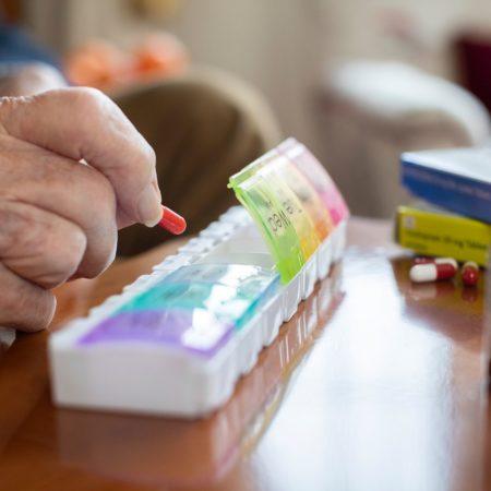 Nahaufnahme eines älteren Mannes, der Medikamente in Tablettenspender organisiert?
