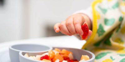 Makro Nahaufnahme der Babyhand mit einem Stück Obst, das im Kinderstuhl sitzt Kind isst gesundes Essen