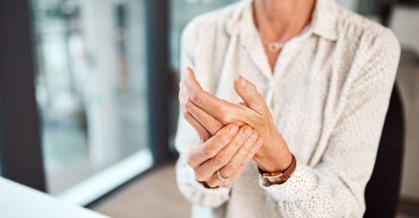 Nahaufnahme einer nicht erkennbaren Geschäftsfrau, die sich bei der Arbeit in einem Büro in der Hand unwohl fühlt discomfort