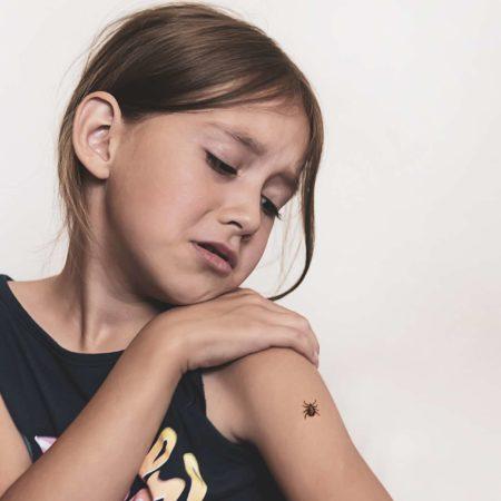 Eine gefährliche Zecke krabbelt auf der Hand des Kindes. Das Mädchen hat Angst vor Insekten.