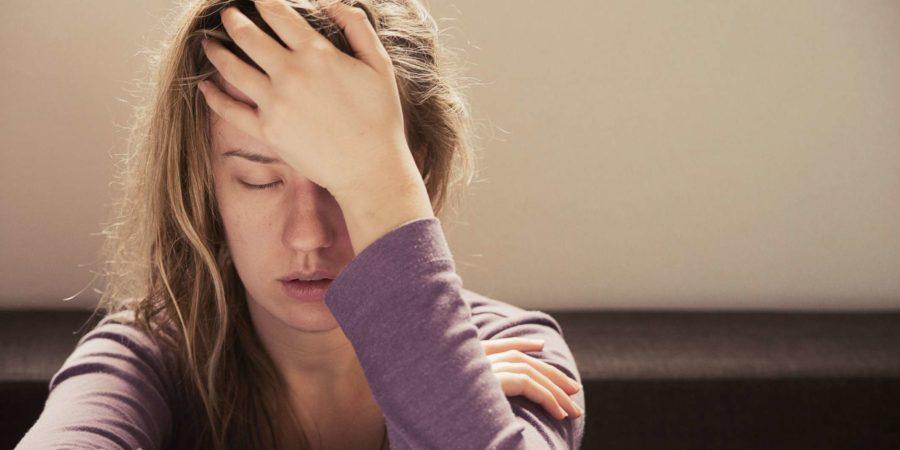 Frau, die unter Stress oder Kopfschmerzen leidet und vor Schmerzen das Gesicht verzieht