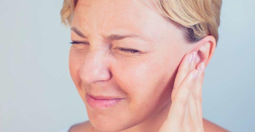 junge Frau mit Ohrenschmerzen, die ihre schmerzhaften Kopfohren berührt