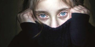 Besorgtes und verängstigtes Mädchen versteckt ihr Gesicht