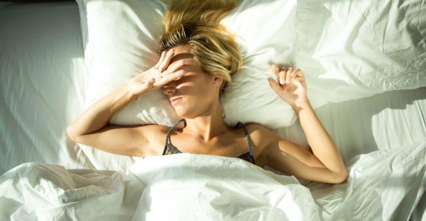 Junge Frau, die durch das Sonnenlicht geweckt wird, das in das Hotelzimmer kommt. Sie bedeckt ihr Gesicht mit ihrer Hand.