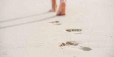 Kaukasische junge Frau, die barfuß im Sand geht, Nahaufnahme.