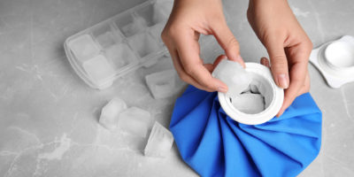 Woman putting ice cubes into pack at marble table, closeup