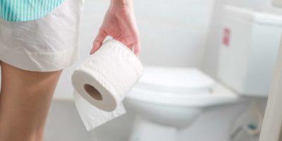 Frau, die Papierrolle hält und an Durchfall in der Toilette leidet.