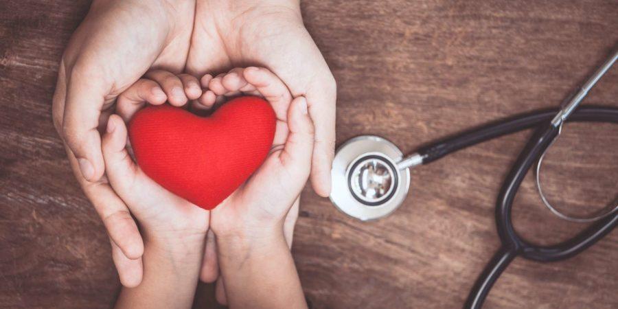 Rotes Herz auf Frauen- und Kinderhänden und mit Stethoskop des Doktors auf hölzernem Hintergrund. Medizinisches Konzept des Gesundheitswesens