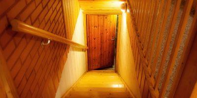 Eine Holztreppe im Haus führt hinunter zur Tür